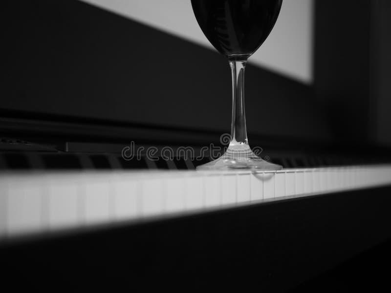 Vidrio de vino tinto en piano, blanco y negro fotografía de archivo