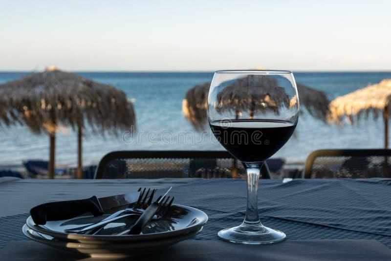 Vidrio de vino tinto en una tabla en la puesta del sol en la playa foto de archivo