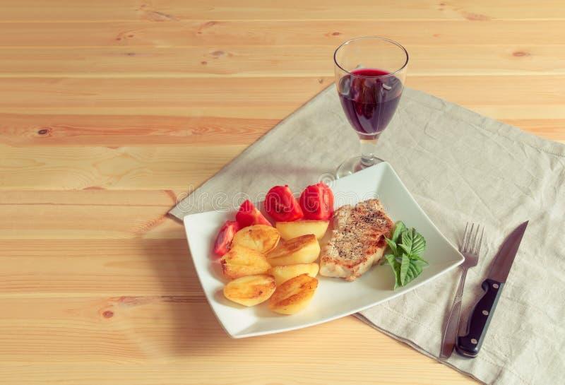 Vidrio de vino tinto y de cerdo asado a la parrilla con la patata asada en la tabla de madera fotos de archivo libres de regalías