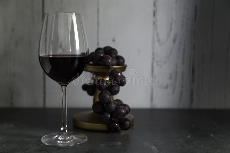 Vidrio de vino tinto y manojo de uvas rojas imagenes de archivo