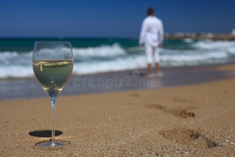 Vidrio de vino, y de las huellas de los hombres en el primer de la playa fotos de archivo libres de regalías