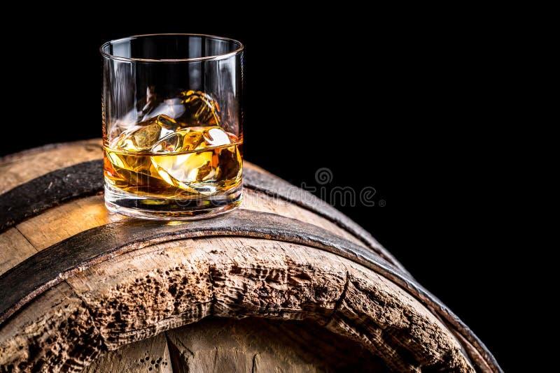 Vidrio de whisky con hielo en barril de madera viejo foto de archivo libre de regalías