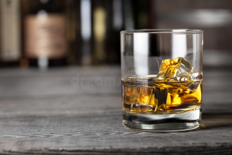 Vidrio de whisky con hielo en el estante de la barra fotos de archivo
