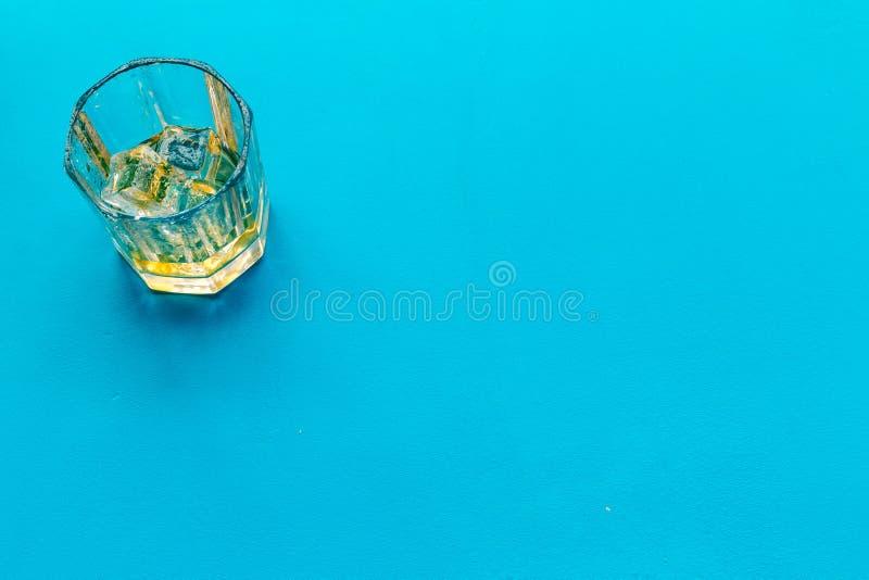 Vidrio de whisky con hielo en espacio azul de la copia de la opinión superior del fondo fotografía de archivo libre de regalías