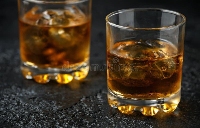 Vidrio de whisky con hielo en fondo rústico foto de archivo libre de regalías