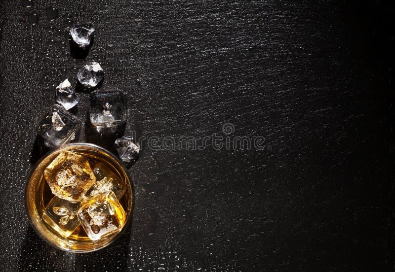 Vidrio de whisky con hielo en la tabla de piedra negra imagenes de archivo