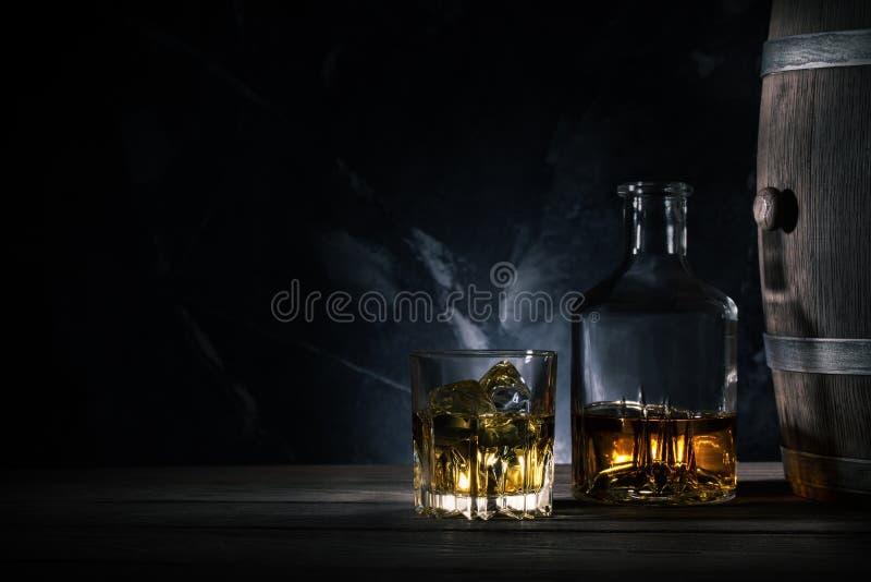 Vidrio de whisky con hielo, la jarra y un barril de madera fotos de archivo libres de regalías