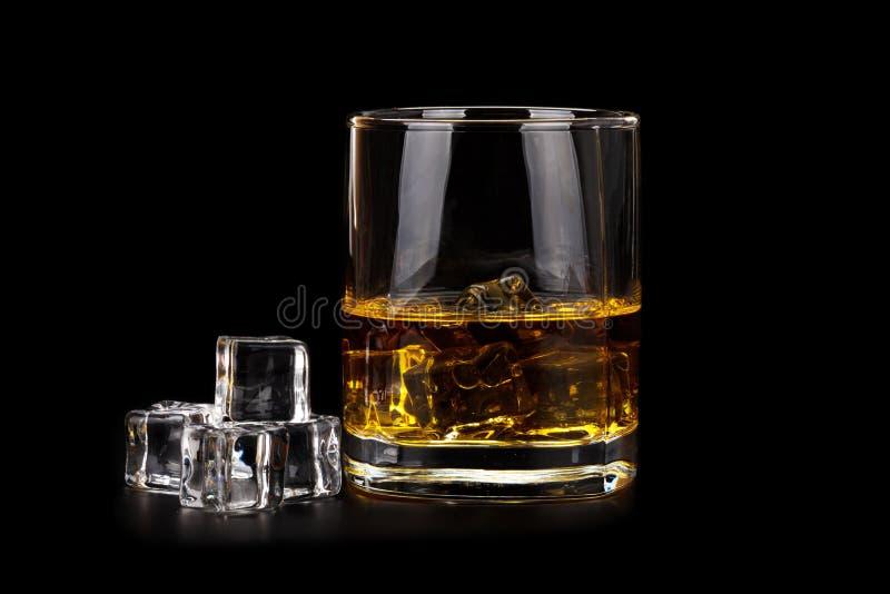 Vidrio de whisky con los cubos de hielo aislados en negro foto de archivo