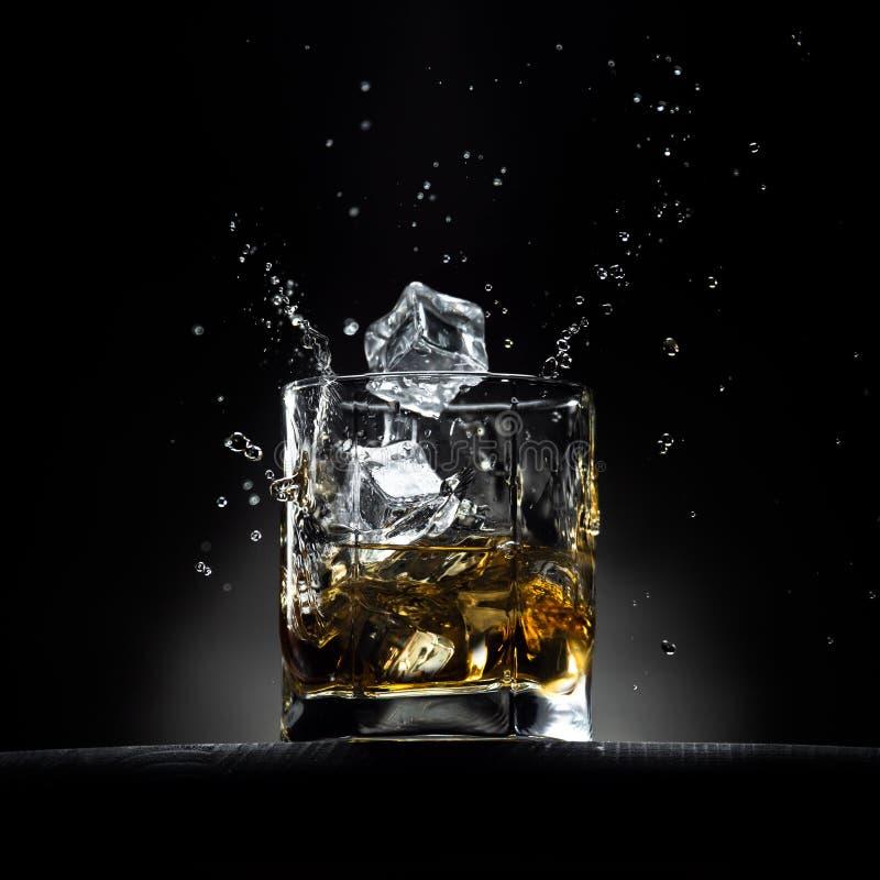 Vidrio de whisky con salpicaduras imágenes de archivo libres de regalías