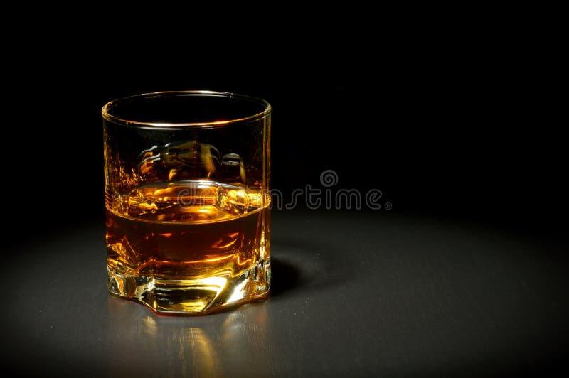 Vidrio de whisky en la tabla negra fotografía de archivo