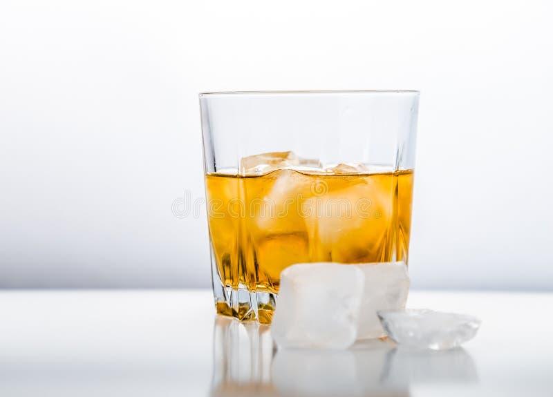 Vidrio de whisky frío en la superficie blanca imagen de archivo libre de regalías