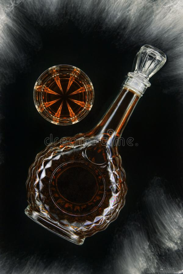 Vidrio de whisky o brandy o coñac con la garrafa en el fondo negro aislado, visión superior imagen de archivo