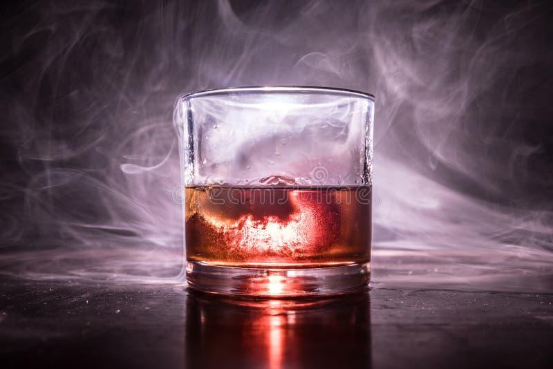 Vidrio de whisky y de hielo en superficie de madera con la luz y la niebla del color en fondo Copie el espacio Tiro de la publici foto de archivo libre de regalías