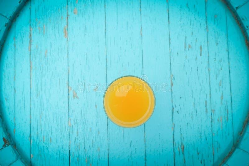 Vidrio de zumo de naranja en la tabla azul del vintage imágenes de archivo libres de regalías