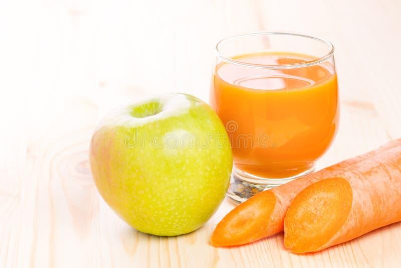 Vidrio de zumo fresco de la zanahoria y de manzana fotografía de archivo