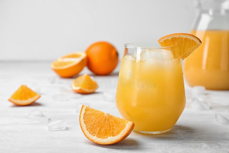 Vidrio de zumo de naranja con los cubos de hielo y cortar la fruta en la tabla imagen de archivo libre de regalías