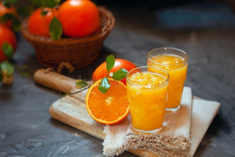 Vidrio de zumo de naranja fresco con las naranjas en la tabla imagen de archivo
