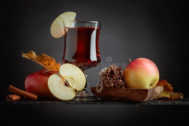 Vidrio de zumo o de sidra de manzana con las manzanas y los palillos de canela jugosos fotos de archivo