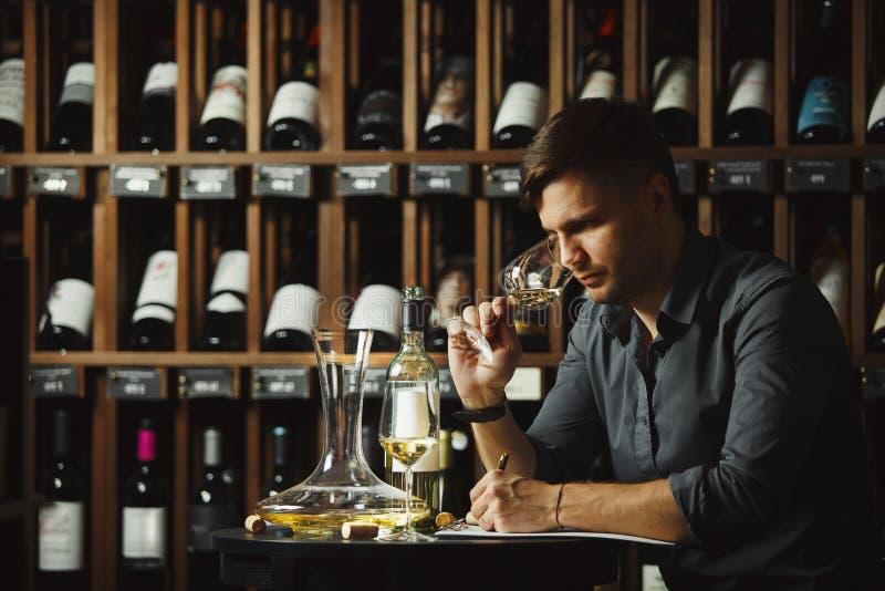 Vidrio degustating del vino blanco del Sommelier vertido foto de archivo libre de regalías