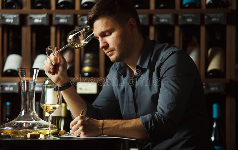 Vidrio degustating del vino blanco del Sommelier vertido foto de archivo