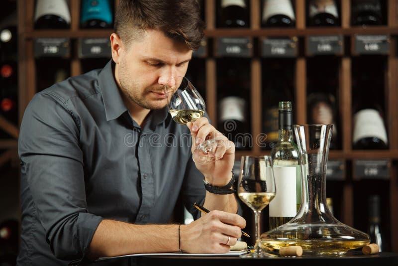 Vidrio degustating del vino blanco del Sommelier vertido imagen de archivo libre de regalías