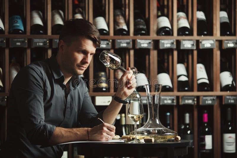 Vidrio degustating del vino blanco del Sommelier vertido imagenes de archivo