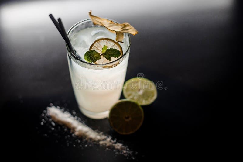 Vidrio del cóctel alcohólico claro adornado con una rebanada de cal imagenes de archivo