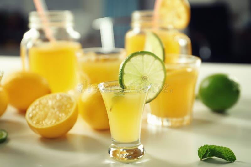 Vidrio del cóctel fresco del limón y rebanada de cal en la tabla ligera fotografía de archivo libre de regalías