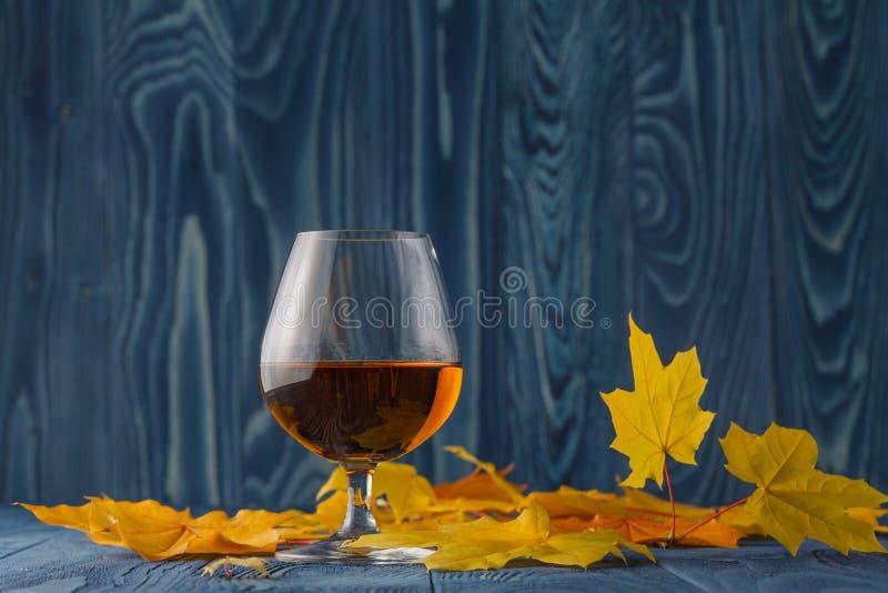 Vidrio del coñac con las hojas de otoño secadas en la tabla imagenes de archivo