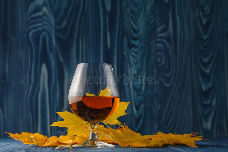 Vidrio del coñac con las hojas de otoño secadas en la tabla imagen de archivo libre de regalías