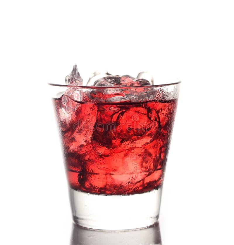 Vidrio del jugo de la cereza, hielo en un fondo blanco foto de archivo libre de regalías