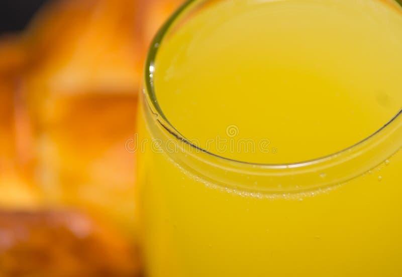 Vidrio del primer de zumo de naranja según lo visto desde arriba, pasteles borrosos en el fondo imagenes de archivo