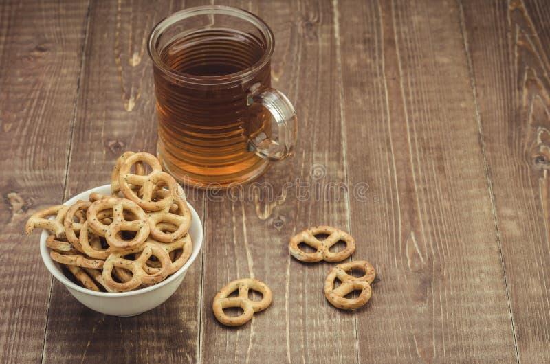 Vidrio del té y del pretzel en una tabla de madera fotos de archivo
