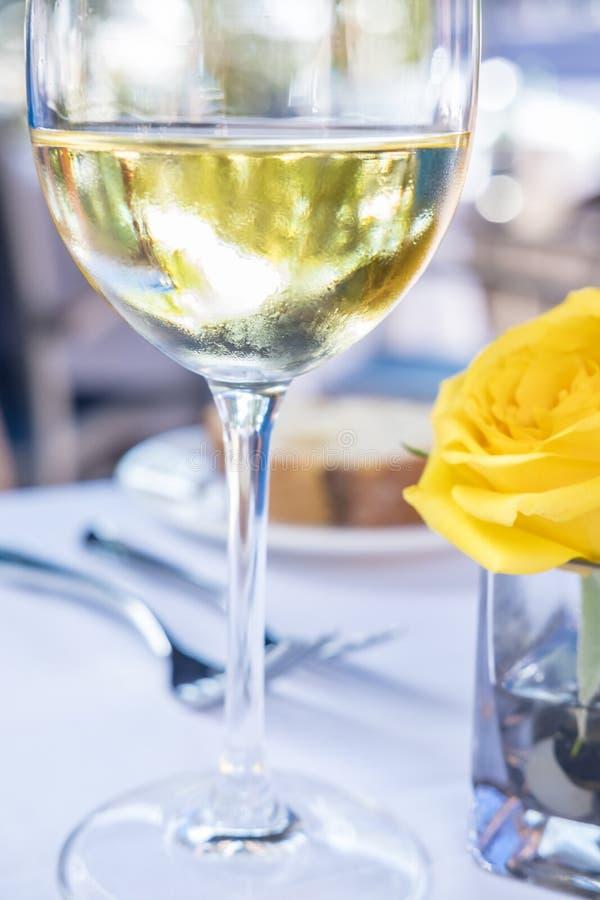 Vidrio del vino blanco y de una Rose amarilla 2 imagenes de archivo