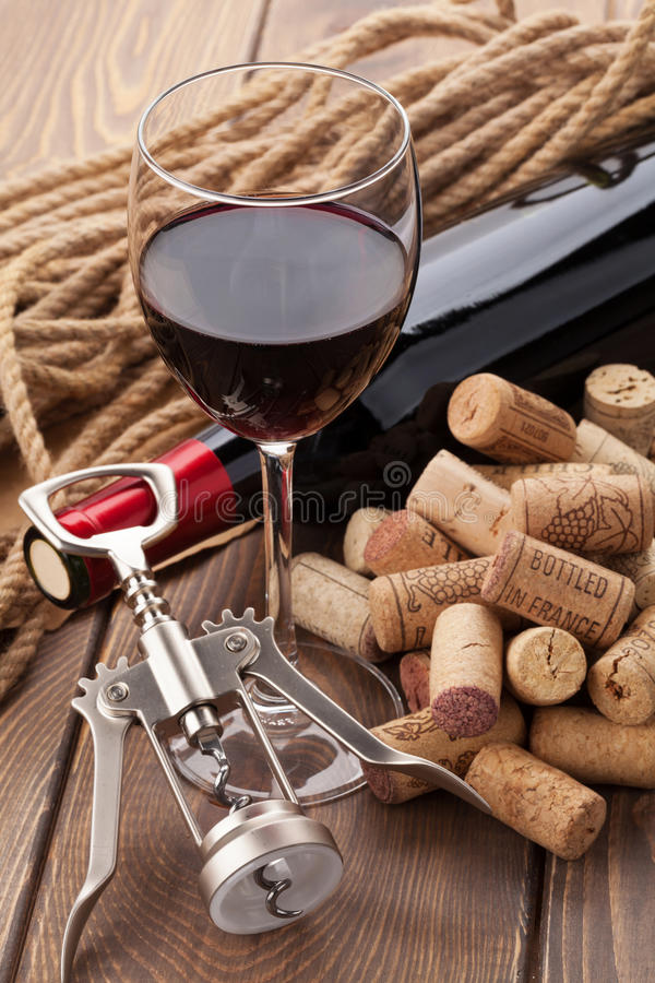 Vidrio del vino rojo, de la botella, del montón de corchos y del sacacorchos fotos de archivo