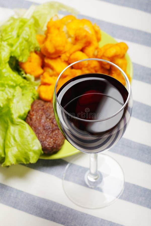Vidrio del vino rojo y de la comida fotografía de archivo
