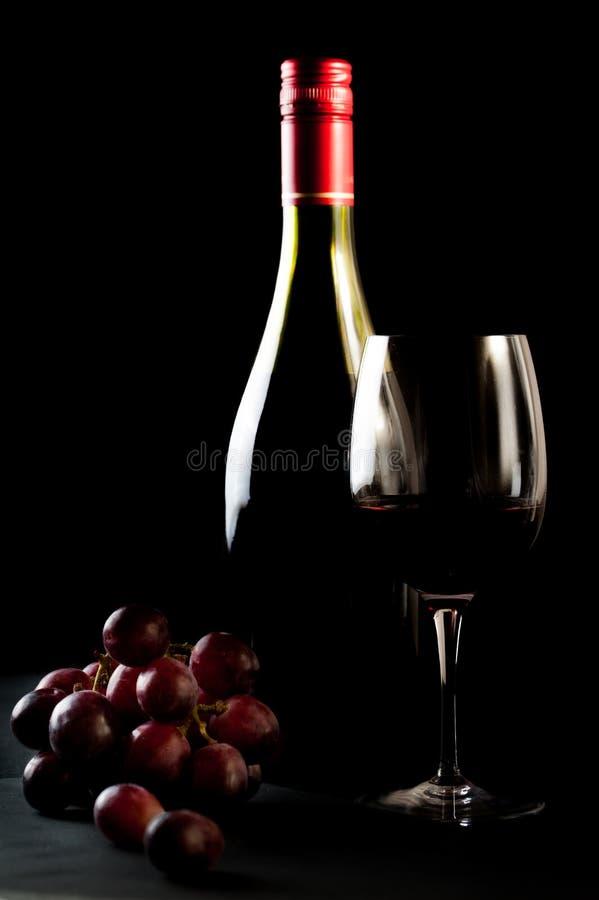 Vidrio del vino tinto con una botella, racimo de uvas fotos de archivo