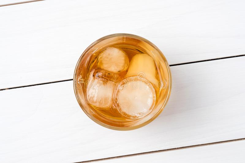 Vidrio del whisky en la tabla de madera blanca imagenes de archivo