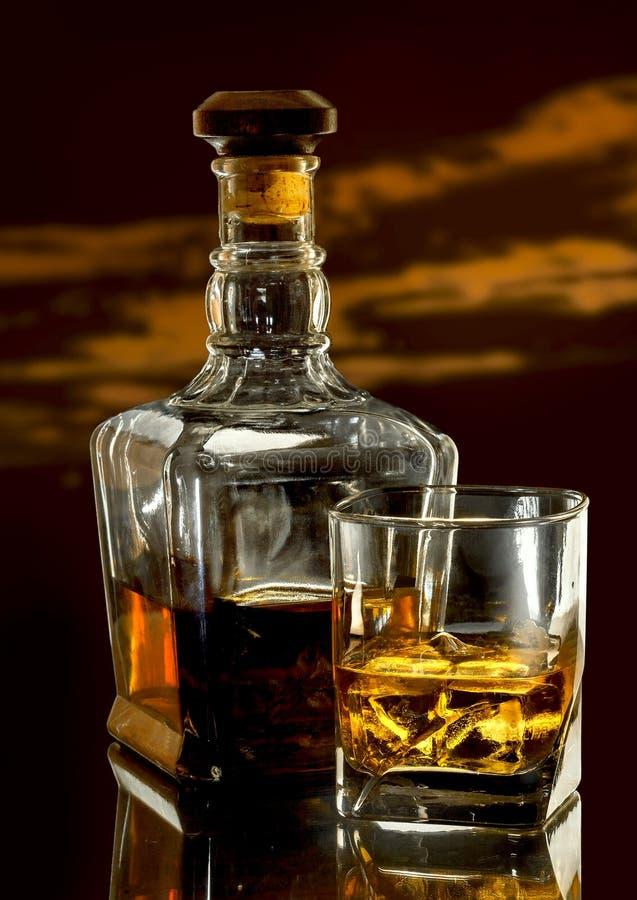 Vidrio del whisky y de la botella elegante en la tabla vidriosa oscura fotografía de archivo libre de regalías