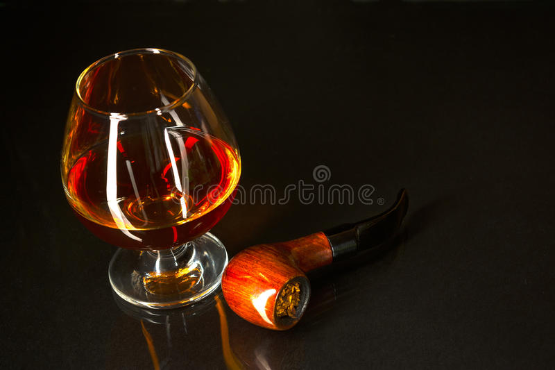 Vidrio del whisky y tubo que fuma en fondo negro fotos de archivo
