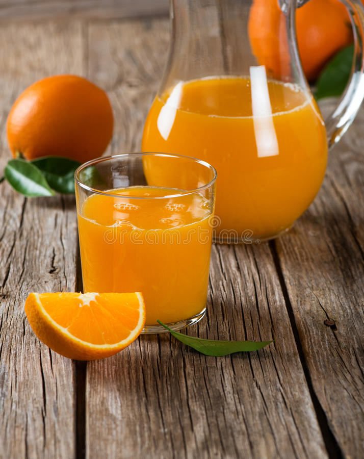 Vidrio del zumo de naranja y naranjas frescas con las hojas imagenes de archivo