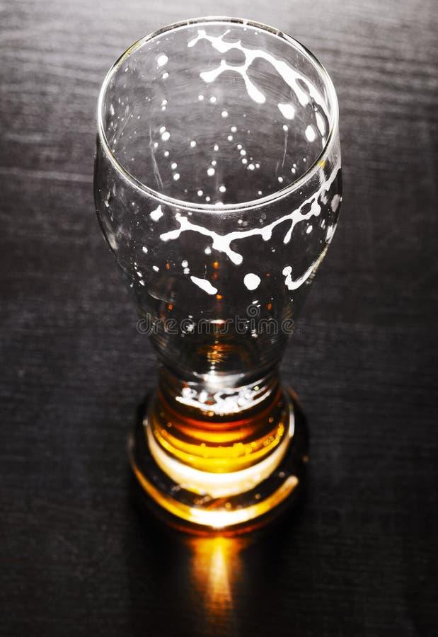 Vidrio drenado de cerveza de cerveza dorada en la tabla imagenes de archivo