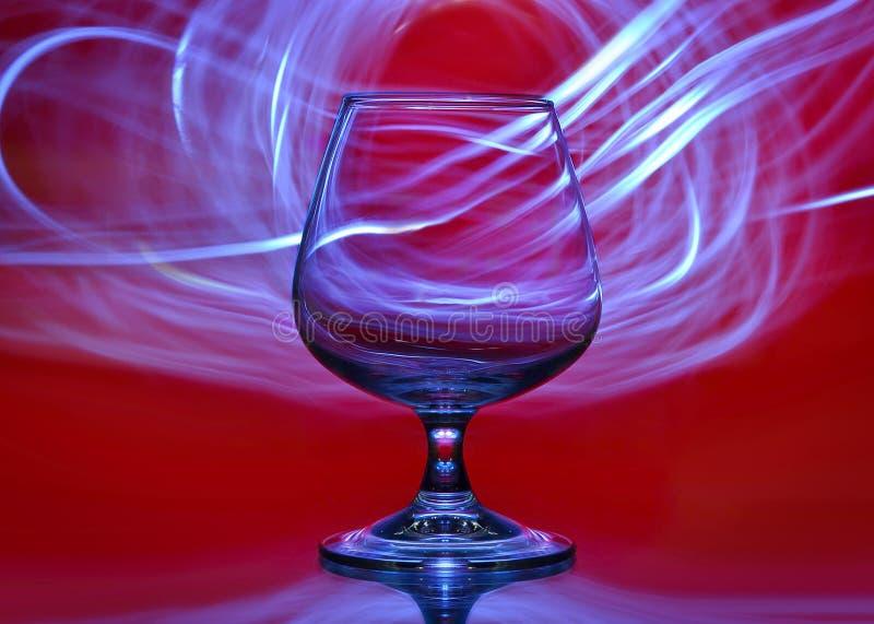 Vidrio en un fondo rojo con las líneas de luz en el fondo fotos de archivo