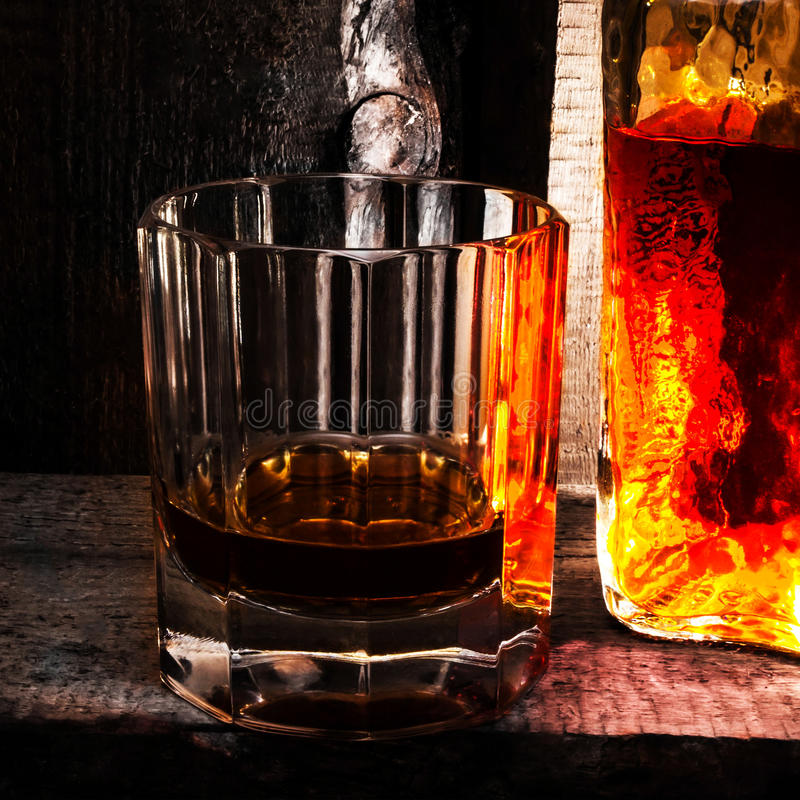 Vidrio escocés del whisky y una botella en viejo fondo de madera. Viejo imagenes de archivo