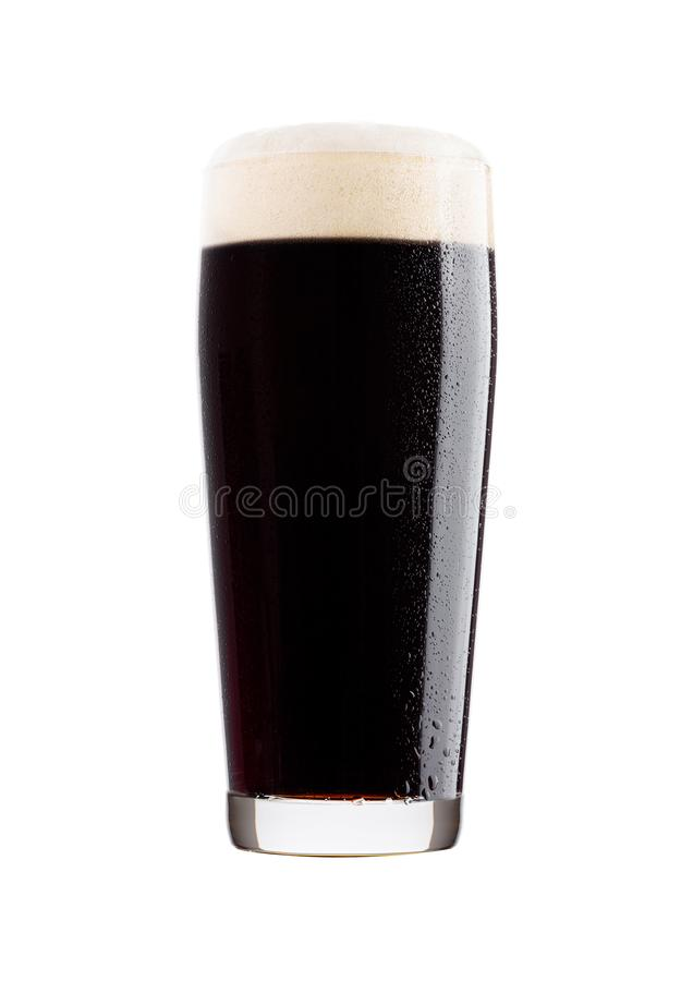 Vidrio frío de cerveza oscura con espuma y rocío foto de archivo libre de regalías