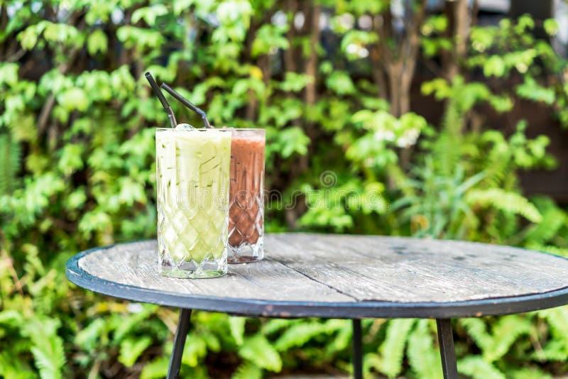 vidrio helado del té verde y del chocolate del matcha en la tabla fotos de archivo