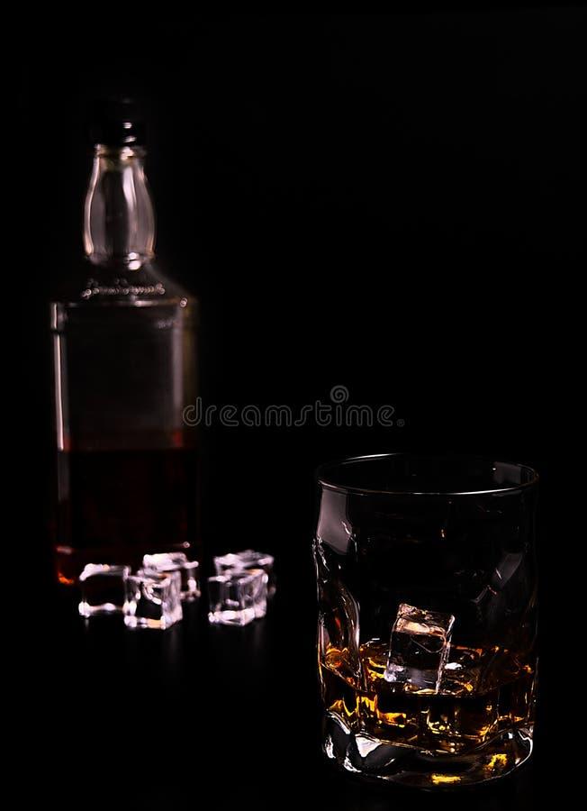 Vidrio, incluyendo los cubos del whisky y de hielo, botella unfocused de whisky en la parte posterior fotografía de archivo libre de regalías