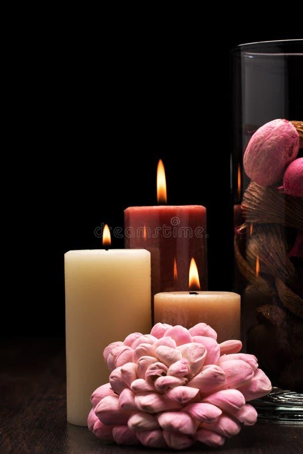 Vidrio llenado de popurrí marrón, rosado y rojo con tres velas encendidas en la tabla de madera con el fondo negro Iluminación de fotografía de archivo libre de regalías