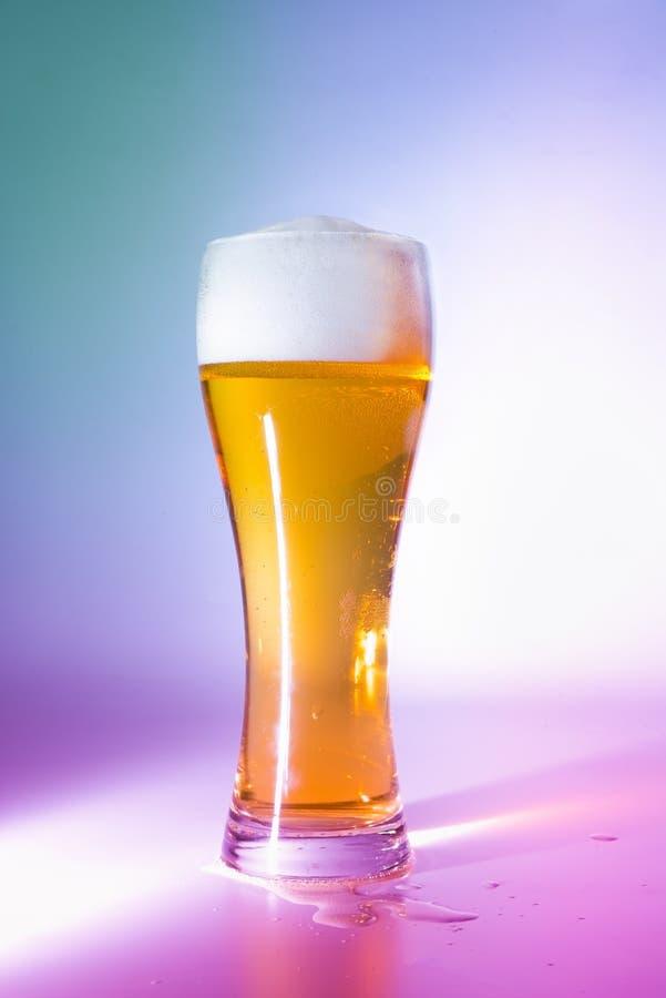 Vidrio lleno de cerveza ligera Luces multicoloras Primer foto de archivo libre de regalías