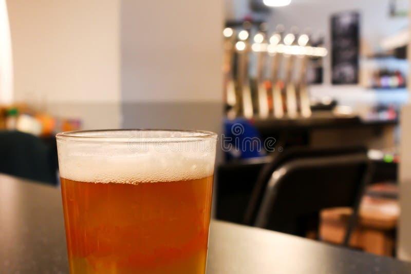 Vidrio lleno de cerveza sabrosa jugosa anaranjada clara en un craf ligero acogedor foto de archivo libre de regalías